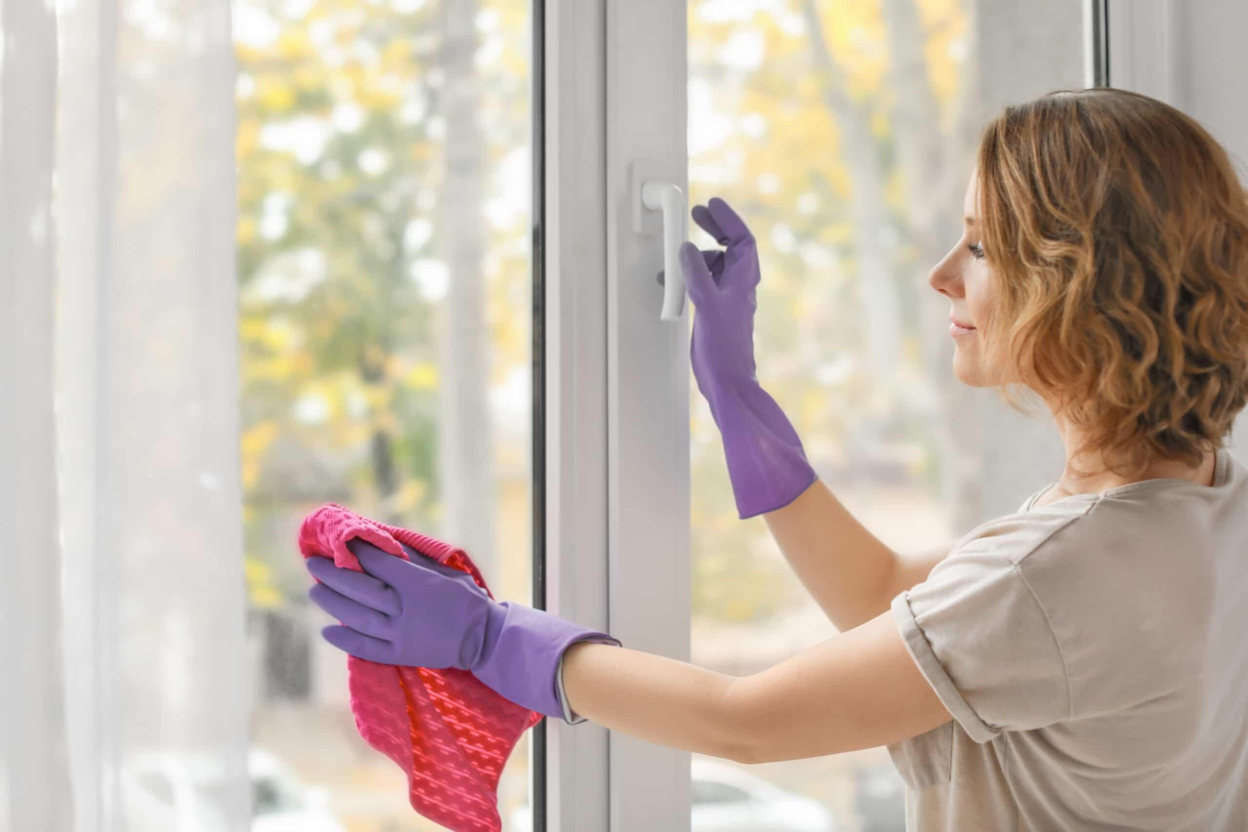 Kotitalousvähennys. Siivousalan ammattilainen pesee ikkunoita.